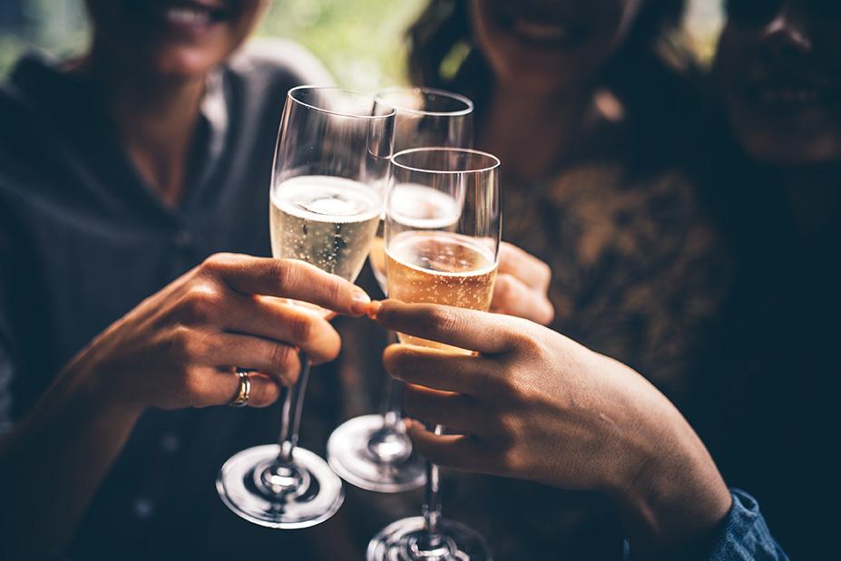 Tre vänner firar med champagne