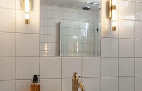 Badrum med vitt kakel och vackra mässingslampor vid sidorna