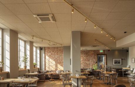 En bistro med bord och stolar, trägolv och fina lampor i taket..