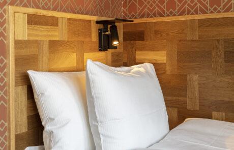 Huvudgaveln på en enkelrumssäng med en lampa som lyser ner.