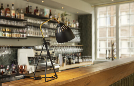 En lampa på en bardisk. I bakgrunden olika flaskor med alkohol.