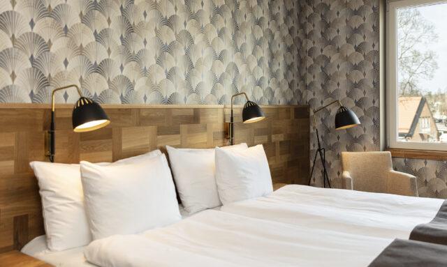 Två sängar ett dubbelrum med blå bruna tapeter samt sänglampa och en golvlampa